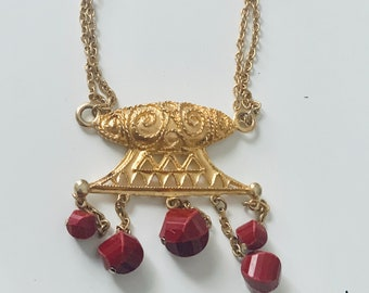 red and gold bead necklace with statement pendant