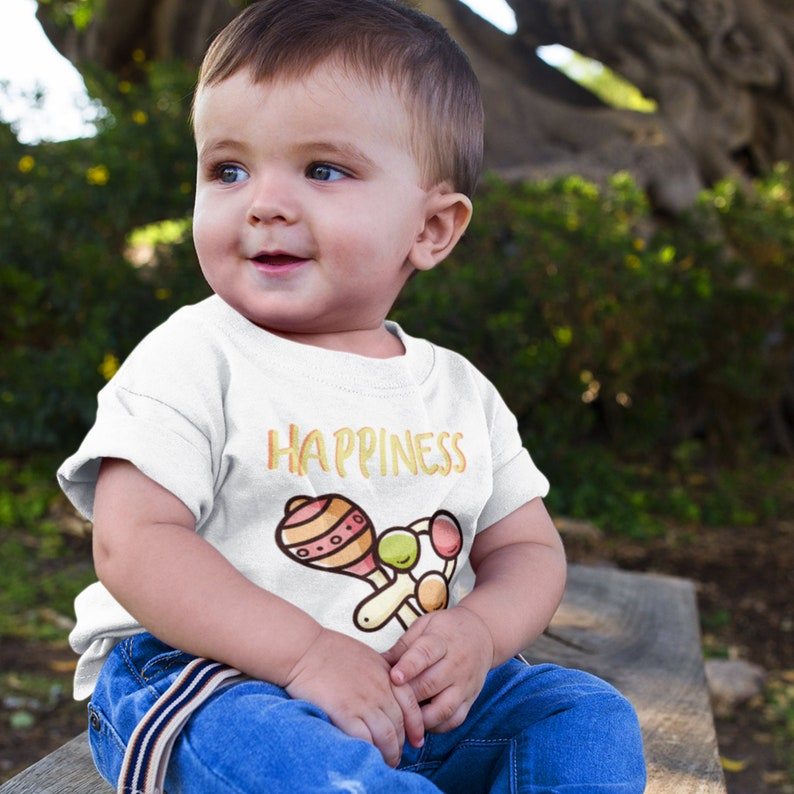 31910c1a992d8 Infant happiness tee written in gold with 2 cute baby rattles on infant  tee. T-shirt available in 3 colors