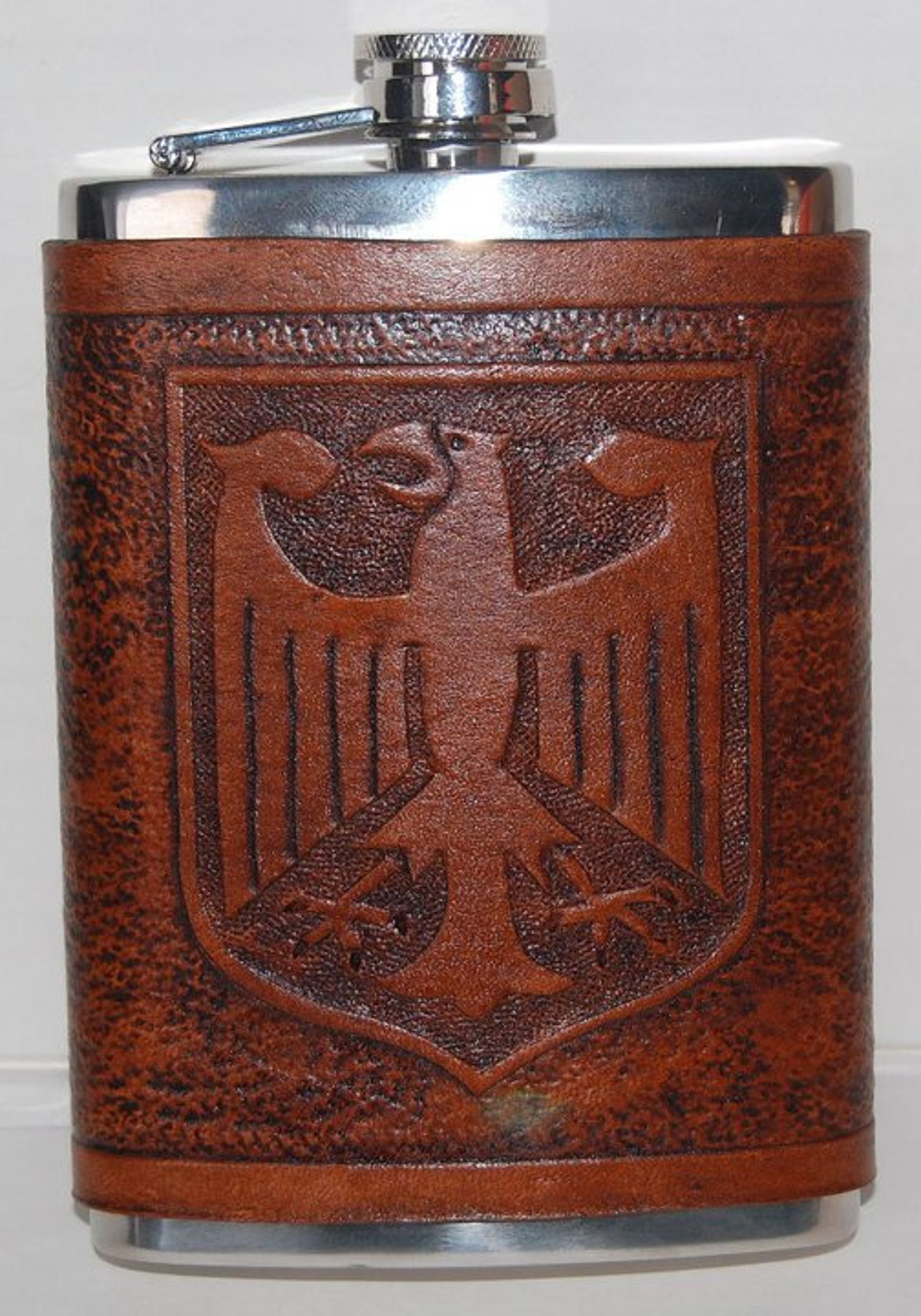 8 ounce stainless steel flask with a leather wrap that has a German Eagle carved in it