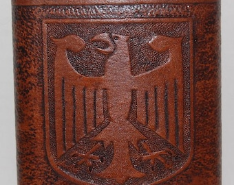 8 ounce stainless steel flask with a leather wrap that has a German Eagle carved in it.