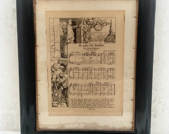 old sheet music behind glass in the ancient wooden frame