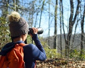 Woman looking through binoculars across valley at mountain view in nature forest during winter without leaves.