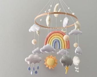 Cloud nursery mobile in pastel color palette with rainbow, sun, stars, rain cloud, snow. Weather baby mobile. Nursery decor with felt balls