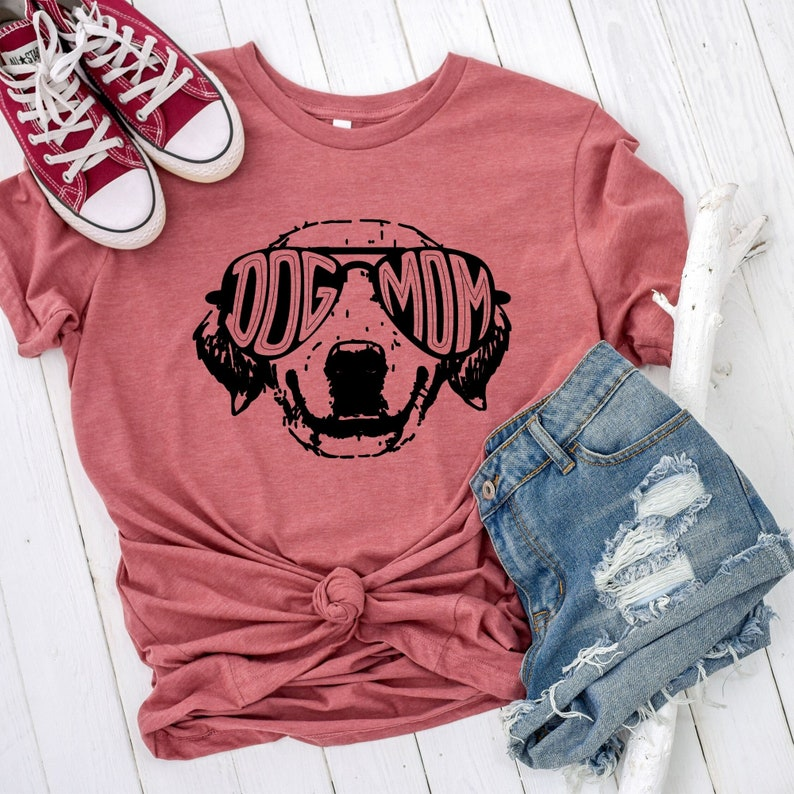 Dog Mom T-Shirt in pink shown with jean shorts and red sneakers.