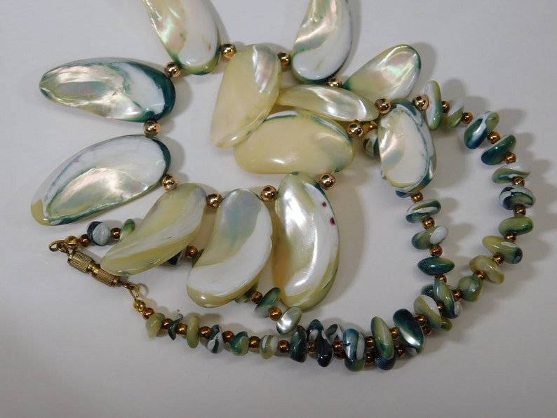 Shell necklace with blue green edges gold spacer beads and barrel clasp