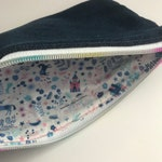 Upcycled denim bag/ pouch/ clutch with a whimsical fairytale land cotton print on the inside w/ a rainbow nylon zipper and mickey head pull.