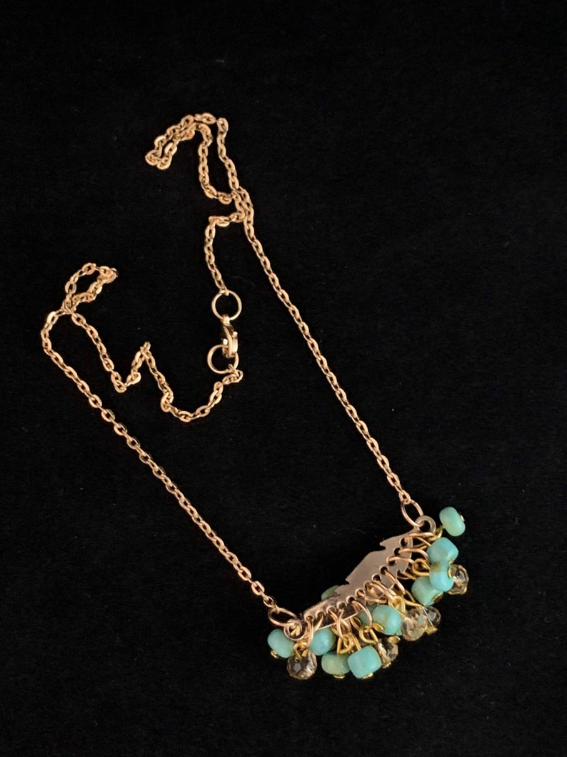 Attached to a gold plated chain. The turquoise feather Gold feather with thick dangling crystal and turquoise colored beads
