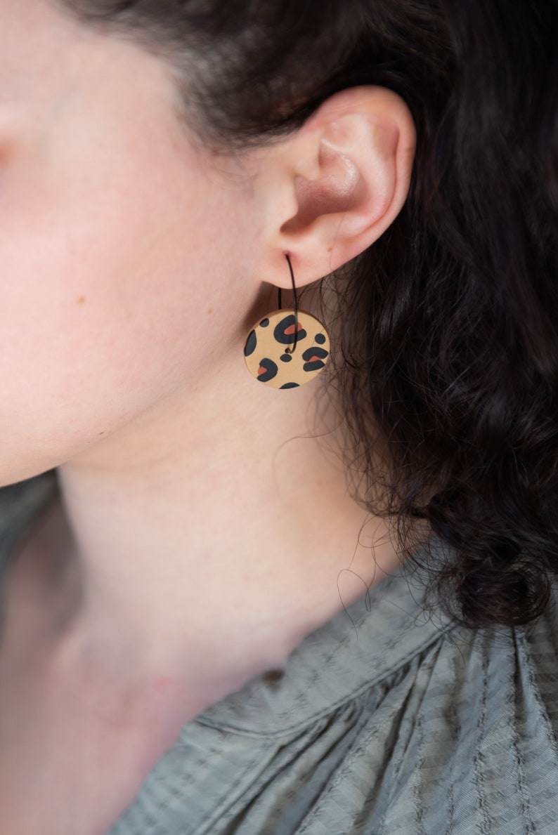 Leopard print earrings on black hoops