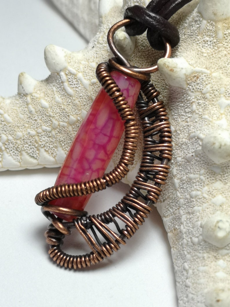 A small pendant made with copper wire woven and wrapped around a dragon vein agate bead..reversible