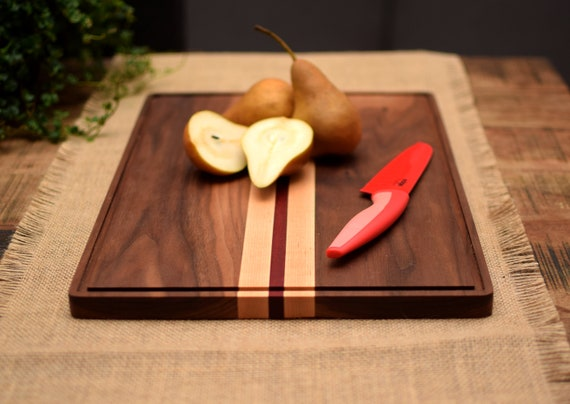 Walnut cutting board with decorative stripe and juice groove.