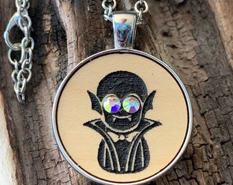 Halloween Dracula in silver tone metal pendant necklace   Spooky but cute black vampire with rhinestone eyes on laser cut wood jewelry.