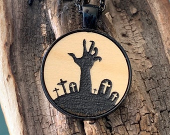 Halloween zombie hand in spooky graveyard black metal necklace. Laser cut Maple wood inserted into Gothic goth jewerly.