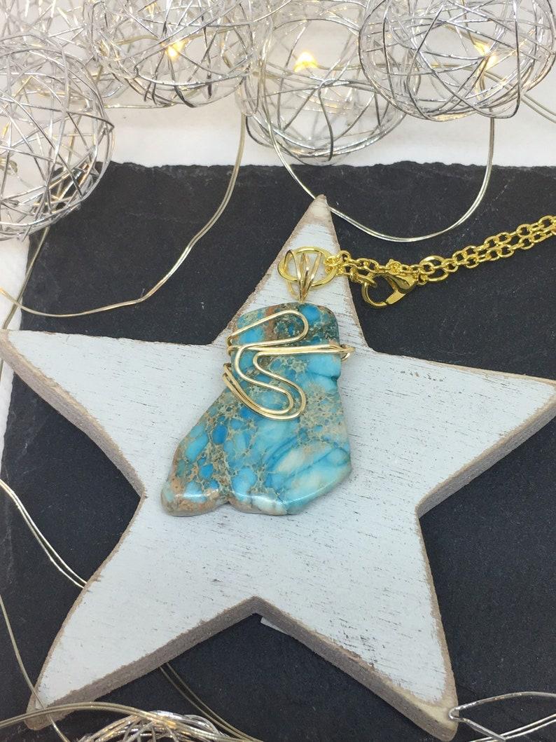 Turquoise jasper irregular shaped stone captured in golden wire pendant