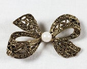 Vintage gold tone filigree bow brooch with faux pearl