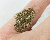 Gold tone filigree ring with floral design, size 4 3/4