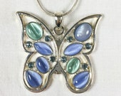 silver tone butterfly pendant with blue and green glass cat eye cabochons and blue rhinestones on adjustable length chain