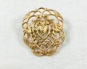 Vintage Monet gold plated filigree brooch, heart or shield, 1980s