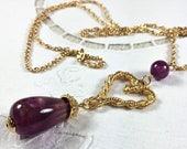 "Avon gold tone heart pendant with purple lucite drop on 30"" rope chain, 1994"