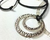 Avon textured silver tone double circle pendant on adjustable length black cord
