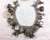 7.25 inch sterling silver charm bracelet (1950s) with 19 charms collected 1950s-1970s, some moveable