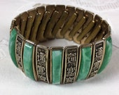 Green and gold tone expansion bracelet with traditional Chinese characters, 1950s
