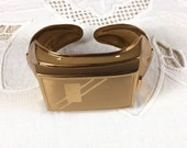 Art Deco Kotler and Kopit wrist compact - brass clamper bracelet with mirror and powder puff, 1940s, K & K