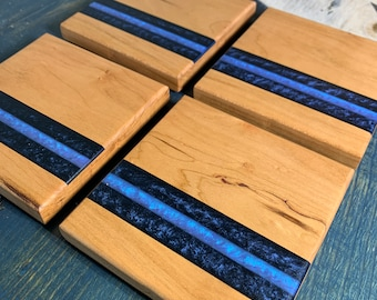 Set of 4 coasters cut from a single piece of cherry wood, with midnight blue and iridescent blue resin inlays