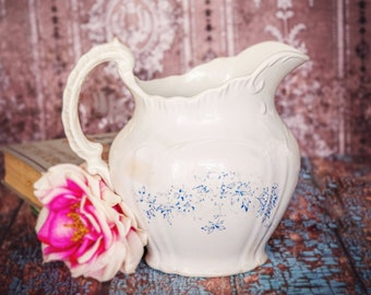 Medium white ironstone water pitcher; dainty blue floral motif; graceful, curved shape and embossing