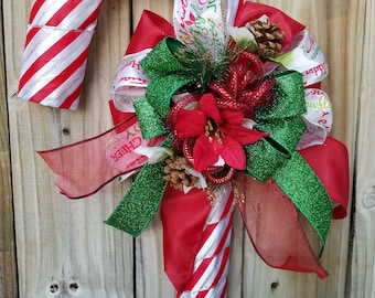 Winter Holiday Candy Cane Christmas Door Covering with a Poinsettia, Red/White Stripes & Green, Red, Printed Ribbon  by Space Coast Crafts
