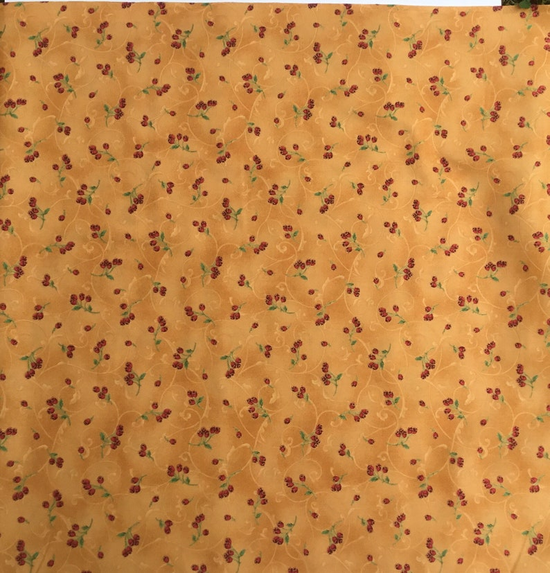 in stock and ready to ship! Red berries with green stems outlined in gold woven quilters cotton sold as yardage