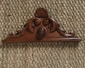 A classic French oak antique carved wooden pediment with naturalist scroll decorative details