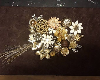 Jewelry collage art:   A Meadow's Bounty.        A golden pallet of vintage brooches and earrings on a patterned faux suede brown backdrop.