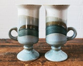 Pair of ceramic espresso mugs. Footed pottery cups with handles. Blue, gray, tan, brown, cream coffee or tea mug.