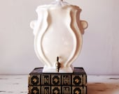 Ceramic wall-mounted fountain. Catholic holy water font. Pottery container with spigot.