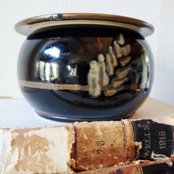 Studio pottery. Pot with lid, signed by Marcia Halperin. Black pottery piece with tan design.