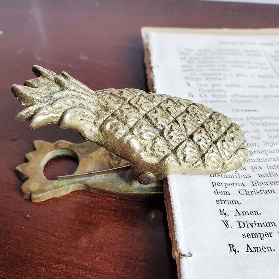 Gold colored metal paper weight. Pineapple shaped paper clip.