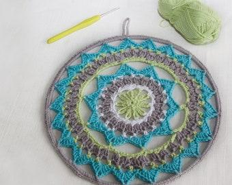 Mandala circular de ganchillo con aro reversible turquesa, gris, verde y blanco.