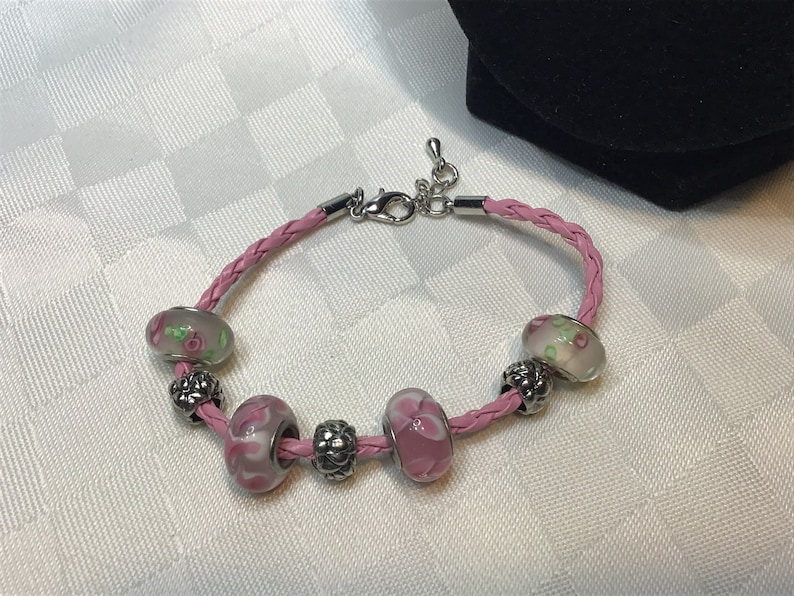 Cute pink leather braid bracelet with flowery glass beads.
