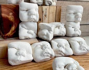 NINE (9) pieces porcelain unglazed smushy baby face decoration