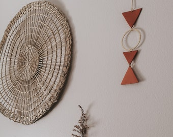 Wall ornament, wall hanging, earth-colored polymer clay triangle, brass ring and gold metal. Interior decoration, wall decoration
