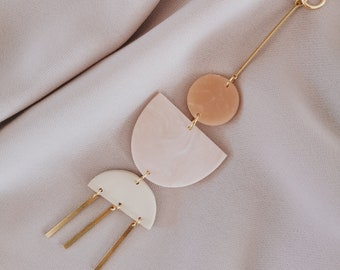 Wall ornament, wall hanging, pink, white and beige polymer clay, brass stem and gold metal. Interior decoration, wall decoration.