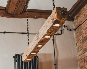 Long wooden lamp with beam hanging on chains in rustic style. Unique wooden lamp with 5 halogens made by hand.