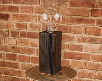 A minimalist wooden table lamp in industrial style. Black table lamp. Original wooden lamp fired with live fire