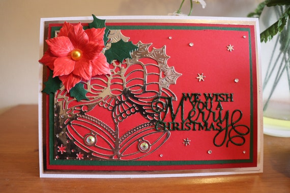 Handmade Christmas Card with Silver Bells and 3D poinsettia flower and foliage on a red background