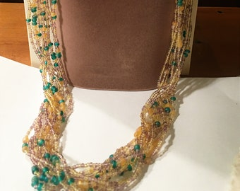 Hand-sewn choker with beads on white green and peach tones.