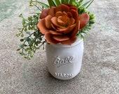 White ceramic mason jar style pot with faux succulent arrangement