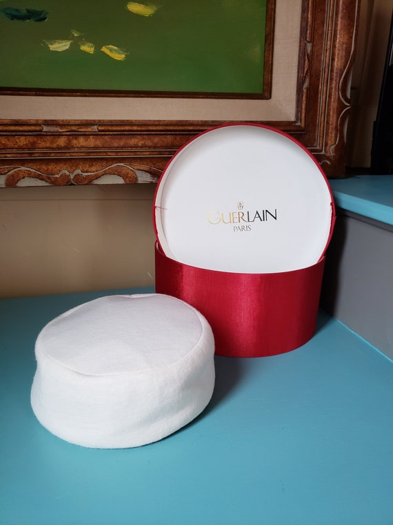 White, winter pill box style hat with red hat box