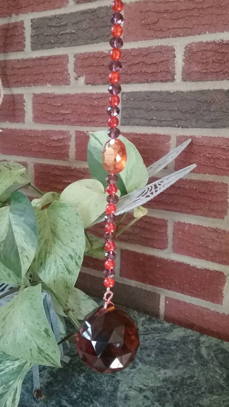 Orange /& maroon  burgundy suncatcher with orange ball prism maroon and orange glass beads and a perfect center faceted orange glass gem!