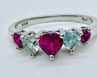 Ruby and the lightest blue, heart shaped, topaz gems set in a sterling band, size 7.