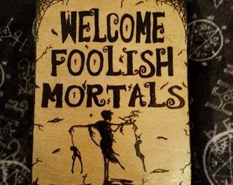 Welcome Foolish Mortals wall hanging.